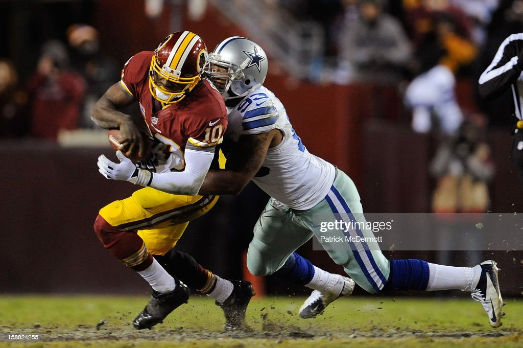 Robert Griffin III #10 of the Washington Redskins is sacked by Anthony Spencer #93 of the Dallas Cowboys in the fourth quarter at FedExField on December 30, 2012 in Landover, Maryland.