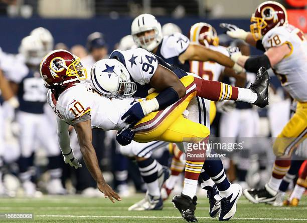 Robert Griffin III of the Washington Redskins is tackled by DeMarcus Ware of the Dallas Cowboys during a Thanksgiving Day game at Cowboys Stadium on...