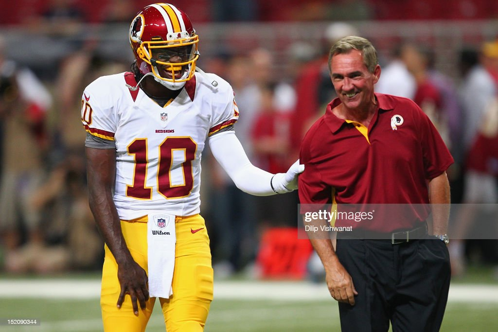 <a gi-track='captionPersonalityLinkClicked' href=/galleries/search?phrase=Robert+Griffin&family=editorial&specificpeople=2495030 ng-click='$event.stopPropagation()'>Robert Griffin</a> III #10 of the Washington Redskins jokes with head coach <a gi-track='captionPersonalityLinkClicked' href=/galleries/search?phrase=Mike+Shanahan&family=editorial&specificpeople=213113 ng-click='$event.stopPropagation()'>Mike Shanahan</a> also of the Washington Redskins during pre-game warm ups prior to playing against the St. Louis Rams at the Edward Jones Dome on September 16, 2012 in St. Louis, Missouri.