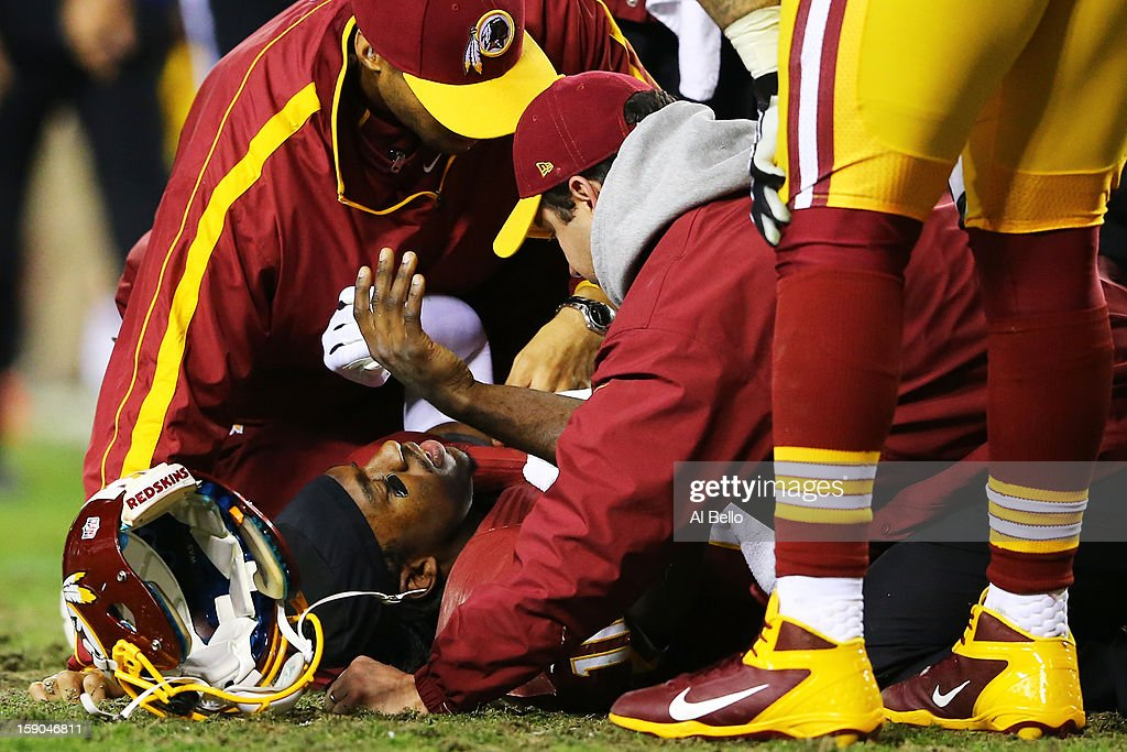 Robert Griffin III #10 of the Washington Redskins receives attention after he was injured on a bad snap in the fourth quarter against the Seattle Seahawks during the NFC Wild Card Playoff Game at FedExField on January 6, 2013 in Landover, Maryland.