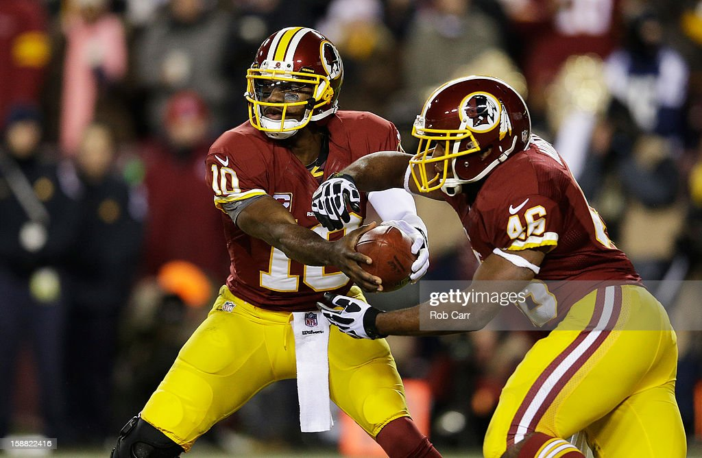 Robert Griffin III #10 runs a play with Alfred Morris #46 of the Washington Redskins in the second quarter against the Dallas Cowboys at FedExField on December 30, 2012 in Landover, Maryland.
