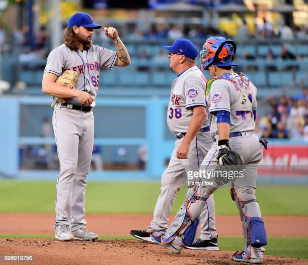 Robert Gsellman of the New York Mets receives a visit from pitching coach Dan Warthen and Rene Rivera during the first inning against the Los Angeles...
