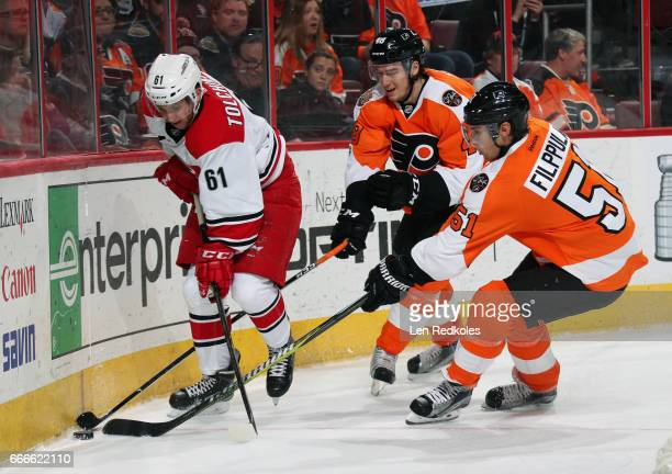 Robert Hagg and Valtteri Filppula of the Philadelphia Flyers battle for the loose puck along the boards with Sergey Tolchinsky of the Carolina...