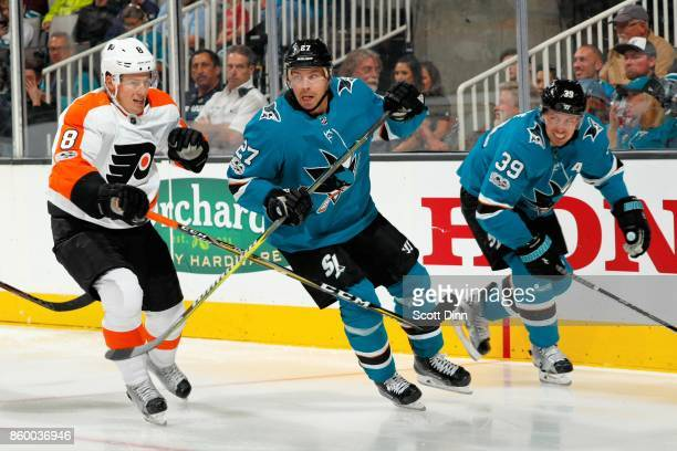 Robert Hagg of the Philadelphia Flyers along with Joonas Donskoi and Logan Couture of the San Jose Sharks skate down the ice during a NHL game at SAP...