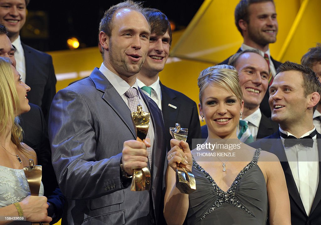 Robert Harting (L), Olympic discus gold medalist, and retired biathlon star Magdalena Neuner hold up their trophies after being awarded Germany's Athlete of the Year 2012 in Baden-Baden, southwestern Germany, on December 16, 2012. AFP PHOTO / THOMAS KIENZLE
