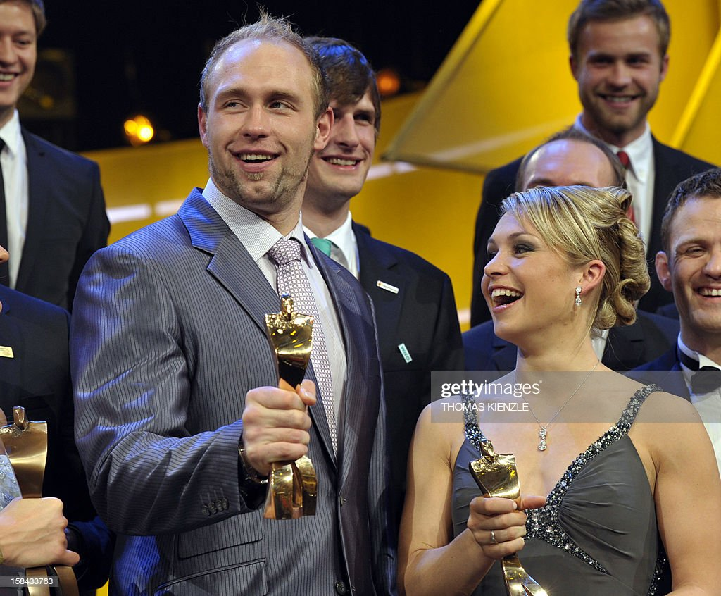 Robert Harting (L), Olympic discus gold medalist, and retired biathlon star Magdalena Neuner hold up their trophies after being awarded Germany's Athlete of the Year 2012 in Baden-Baden, southwestern Germany, on December 16, 2012.