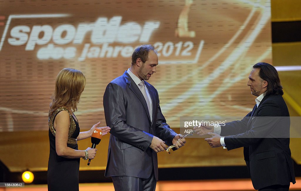 Robert Harting (C), Olympic discus gold medalist, receives the trophy by phgotographer Alexander von Hassenstein (R) after being awarded Germany's Athlete of the Year 2012 in Baden-Baden, southwestern Germany, on December 16, 2012. AFP PHOTO / THOMAS KIENZLE