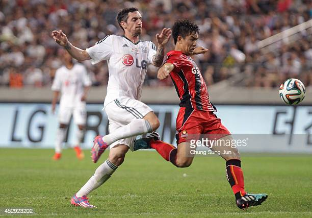 Robert Hilbert of Bayer Leverkusen compete for the ball with Lee WoongHee of FC Seoul during the match between Bayer Leverkusen and FC Seoul as a...