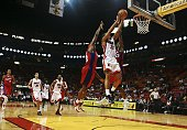 Robert Hite of the Miami Heat goes to the basket over Elton Brand and Quinton Ross of the Los Angeles Clippers at American Airlines Arena on January...