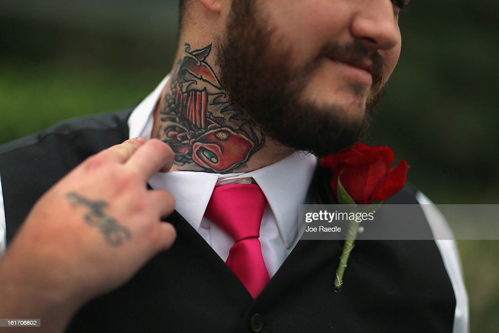 Robert Homa shows off the tattoo he said he put on his neck to cover another tattoo which was his old girlfriend's name as he participates during a group Valentine's day wedding at the National Croquet Center on February 14, 2013 in West Palm Beach, Florida. The group wedding ceremony is put on by the Palm Beach Country Clerk & Comptroller's office and approximately 40 couple tied the knot.