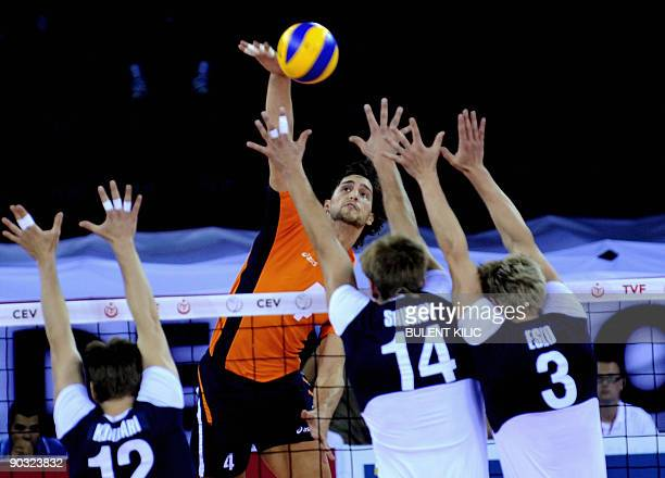 Robert Horstink of The Netherlands spikes the ball over the net as Finland's Olli Kunnari Konstantin Shumov and Mikko Esko attempt to block it during...