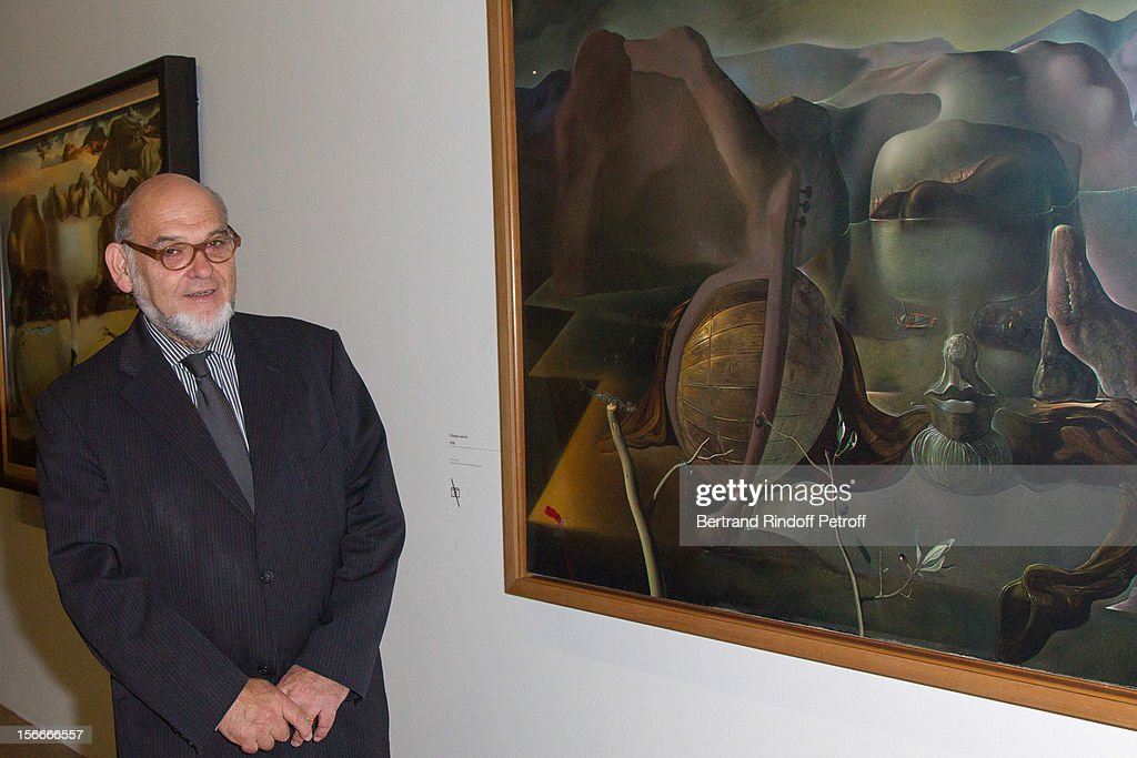 Robert Hue poses by Salvador Dali's 1938 oil on canvas 'Enigma without end' as he attends Dali Private Exhibition Preview at Centre Pompidou on November 18, 2012 in Paris, France.