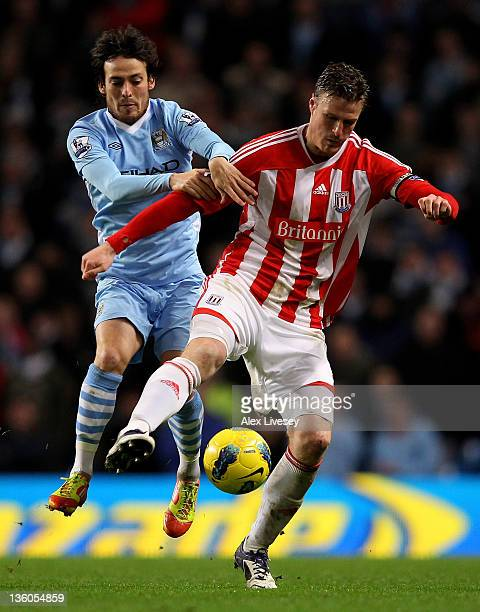 Robert Huth of Stoke City tangles with David Silva of Manchester City during the Barclays Premier League match between Manchester City and Stoke City...