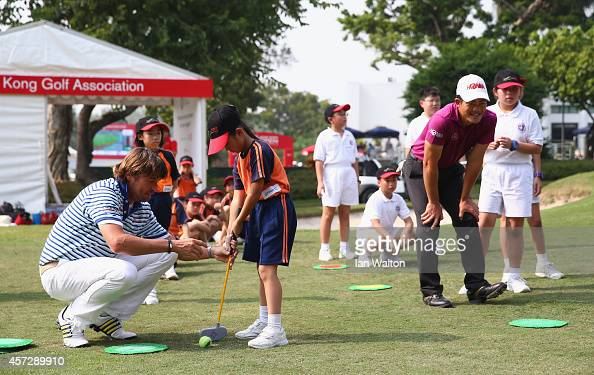 Robert Jan Derksen of The Netherlands and Liang WenChong of China take part in a kids golf clinic during the first round of the 2014 Hong Kong open...