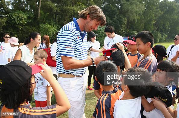 Robert Jan Derksen of The Netherlands takes part in a kids golf clinic during the first round of the 2014 Hong Kong open at The Hong Kong Golf Club...