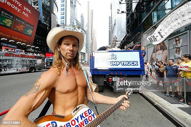 Robert John Burck known as the Naked Cowboy attends 2014 National Toilet Paper Day at Times Square on August 26 2014 in New York City