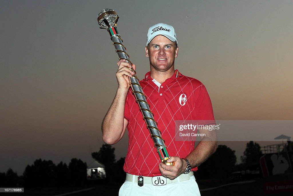 Robert Karlsson of Sweden proudly holds the Dubai World Championship trophy after his second hole sudden death victory over Ian Poulter in the final...
