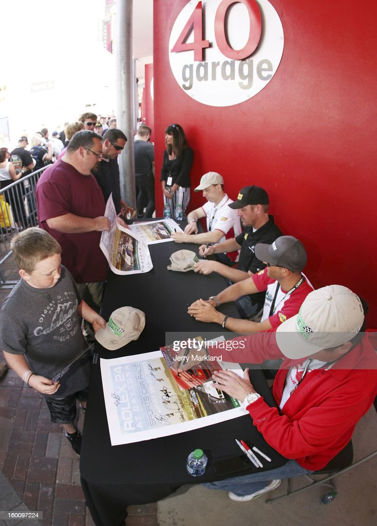 Robert Kauffman (l), Clint Bowyer, Rui Aguas and Michael Waltrip (r) drivers of the #56 AF-Waltrip RK Motors Ferrari 458 sign autographs at the Rolex 24 at Daytona International Speedway on January 26, 2013 in Daytona Beach, Florida.