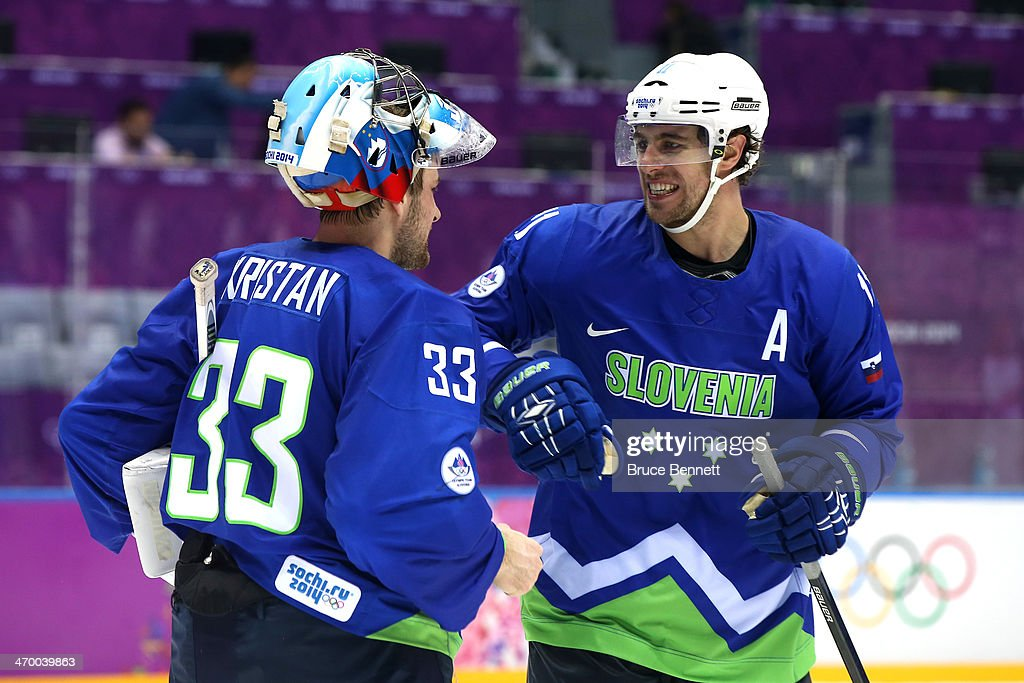 Robert Kristan of Slovenia celebrates with teammate Anze Kopitar after defeating Austria 4 to 0 in the Men's Ice Hockey Qualification Playoff game on...