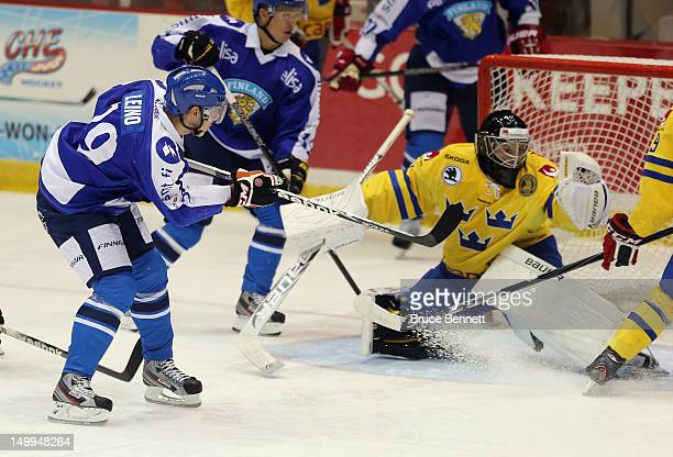 Robert Leino of Team Finland is stopped by Oscar Dansk of Team Sweden at the USA hockey junior evaluation camp at the Lake Placid Olympic Center on...