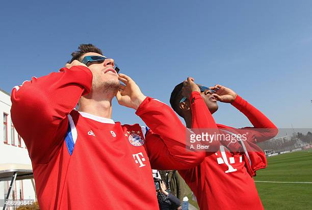 Robert Lewandowski and David Alaba of Bayern Muenchen watch a penumbral solar eclipse before a training session at the FC Bayern Muenchen training...
