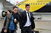 Robert Lewandowski and his fiance Anna Stachurska walk across the tarmac as the Borussia Dortmund return to Dortmund Airport after UEFA Champions...