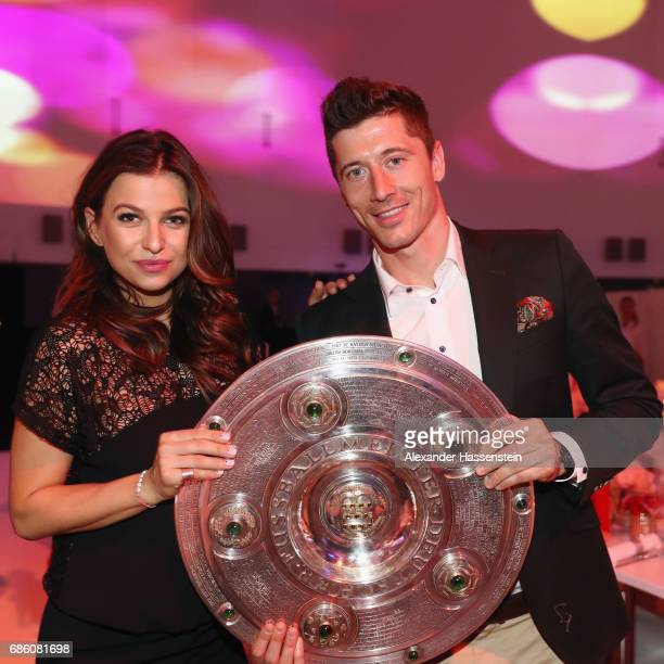 Robert Lewandowski and his wife Anna Stachurska pose with the trophy during the FC Bayern Muenchen Championship party following the Bundesliga match...