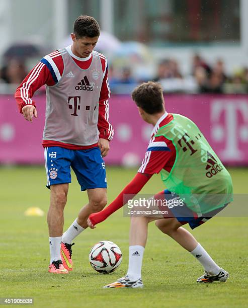 Robert Lewandowski and Lucas Scholl of Bayern Muenchen fight for the ball during a training session at Bayern's training ground Saebener strasse on...