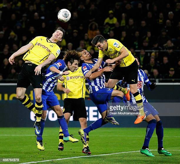 Robert Lewandowski and Nuri Sahin of Dortmund and Hajime Hosogai and Marcel Ndjeng of Hertha challenge for the header during the Bundesliga match...