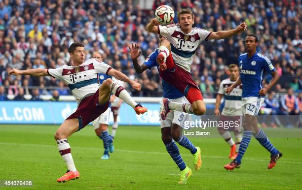 Robert Lewandowski and Thomas Mueller of Muenchen jump for the ball during the Bundesliga match between FC Schalke 04 and FC Bayern Muenchen at...