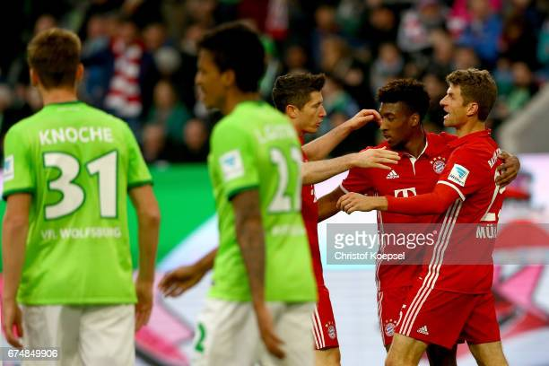 Robert Lewandowski celebrates the second goal with Kingsley Coman and Thomas Mueller of Bayern Muenchen during the Bundesliga match between VfL...