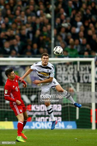 Robert Lewandowski of Bayern Muenchen and Andreas Christensen of Moenchengladbach go up for a header during the Bundesliga match between Borussia...