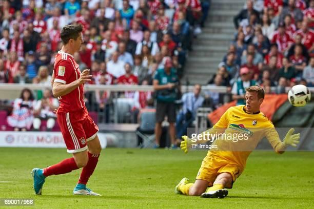 Robert Lewandowski of Bayern Muenchen and Goalkeeper Alexander Schwolow of Freiburg battle for the ball during the Bundesliga match between Bayern...