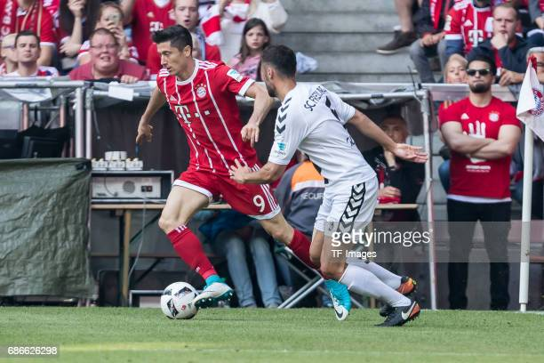 Robert Lewandowski of Bayern Muenchen and Manuel Gulde of Freiburg battle for the ball during the Bundesliga match between Bayern Muenchen and SC...