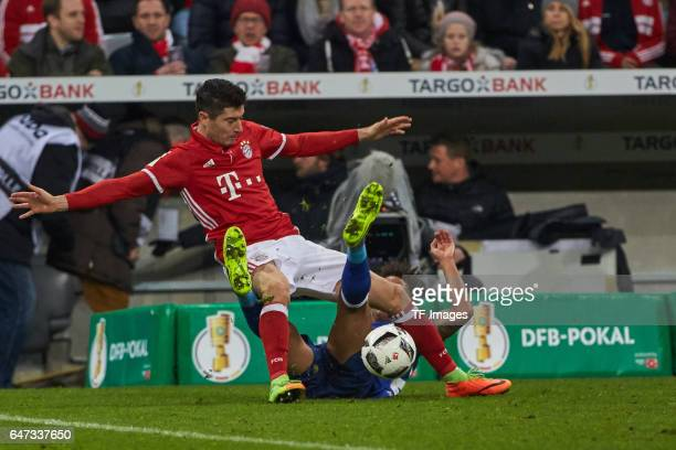 Robert Lewandowski of Bayern Muenchen and Thilo Kehrer of Schalke battle for the ball during the DFB Cup quarter final between Bayern Muenchen and FC...