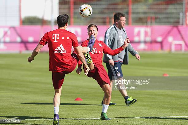 Robert Lewandowski of Bayern Muenchen battles for the ball with his team mate Mario Goetze during a training session at Bayern Muenchen's trainings...