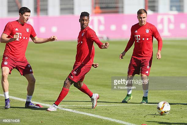 Robert Lewandowski of Bayern Muenchen battles for the ball with his team mates Kingsley Coman and Mario Goetze during a training session at Bayern...