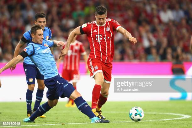 Robert Lewandowski of Bayern Muenchen battles for the ball with Dominik Kohr of Leverkusen during the Bundesliga match between FC Bayern Muenchen and...