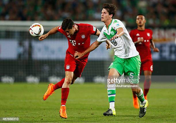 Robert Lewandowski of Bayern Muenchen battles for the ball with Timm Klose of VfL Wolfsburg during the DFL Supercup match between VfL Wolfsburg and...