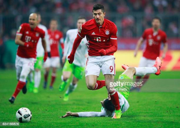 Robert Lewandowski of Bayern Muenchen breaks away from Ricardo Rodriguez of VfL Wolfsburg during the DFB Cup Round Of 16 match between Bayern...