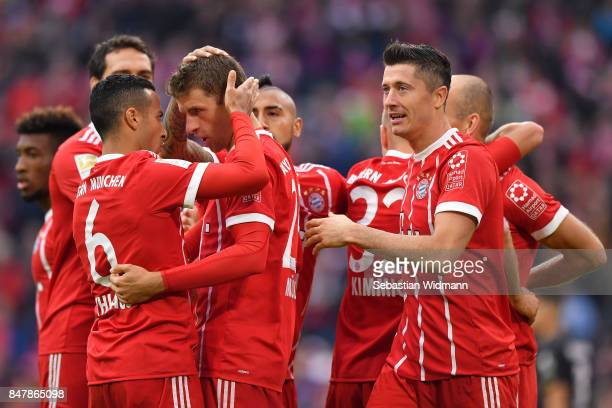 Robert Lewandowski of Bayern Muenchen celebrates after he scored his teams third goal to make it 30 with Thiago Alcantara of Bayern Muenchen and...