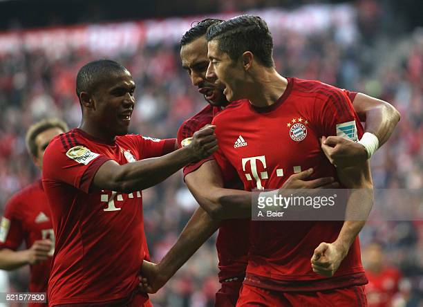Robert Lewandowski of Bayern Muenchen celebrates his first goal together with teammates Douglas Costa and Medhi Benatia during the Bundesliga match...