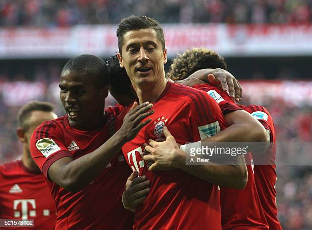 Robert Lewandowski of Bayern Muenchen celebrates his first goal together with teammate Douglas Costa and others during the Bundesliga match between...