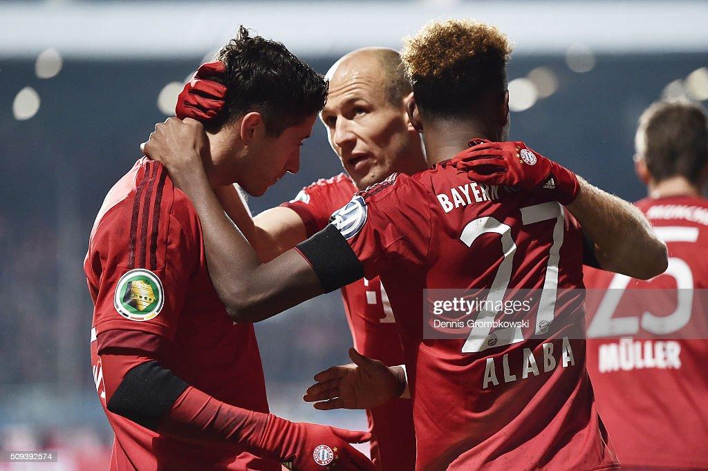 Robert Lewandowski of Bayern Muenchen celebrates scoring his side's first goal with Arjen Robben and David Alaba of Bayern Muenchen during the DFB...