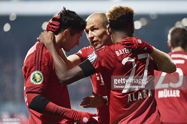 Robert Lewandowski of Bayern Muenchen celebrates scoring his side's first goal with Arjen Robben and David Alaba of Bayern Muenchen during the DFB...