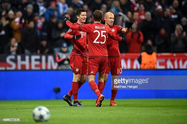 Robert Lewandowski of Bayern Muenchen celebrates scoring his teams second goal with team mates Thomas Mueller and Arjen Robben during the UEFA...