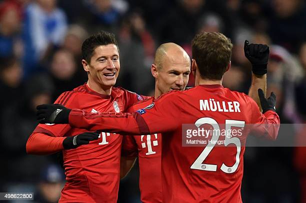 Robert Lewandowski of Bayern Muenchen celebrates scoring his teams second goal with team mates Thomas Mueller and Arjen Robben during the UEFA...