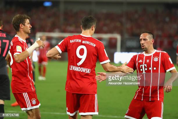 Robert Lewandowski of Bayern Muenchen celebrates scoring the opening goal with his team mates Thomas Mueller and Franck Ribery during the Audi...