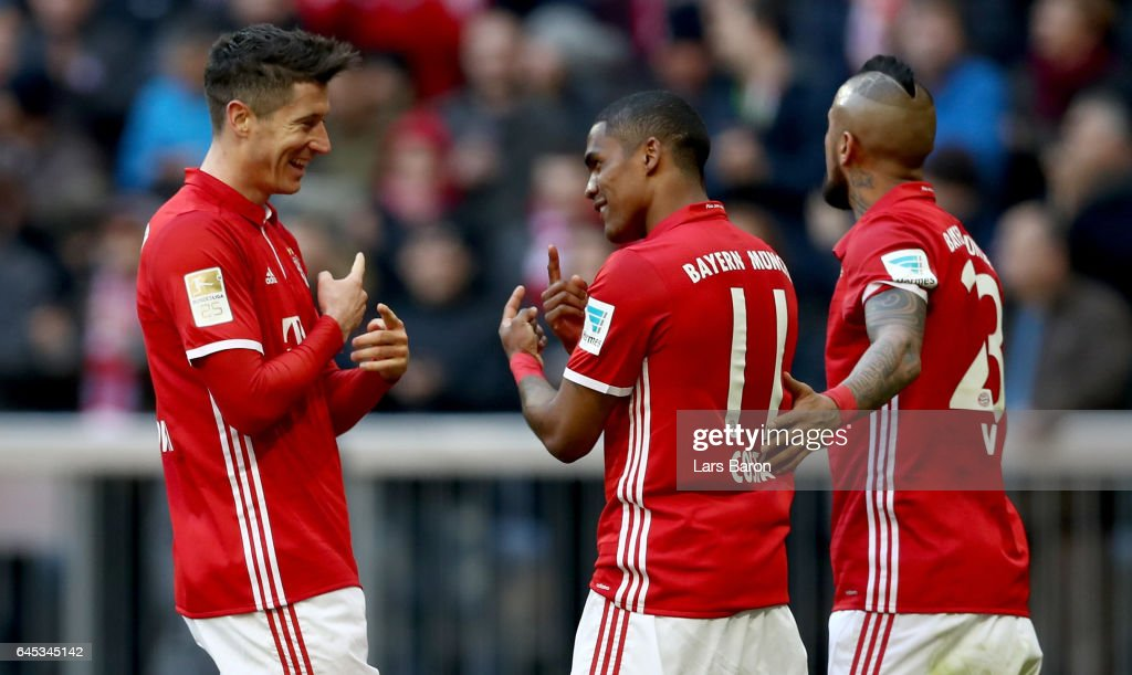 Robert Lewandowski of Bayern Muenchen celebrates with Douglas Costa of Bayern Muenchen during the Bundesliga match between Bayern Muenchen and Hamburger SV at Allianz Arena on February 25, 2017 in Munich, Germany.