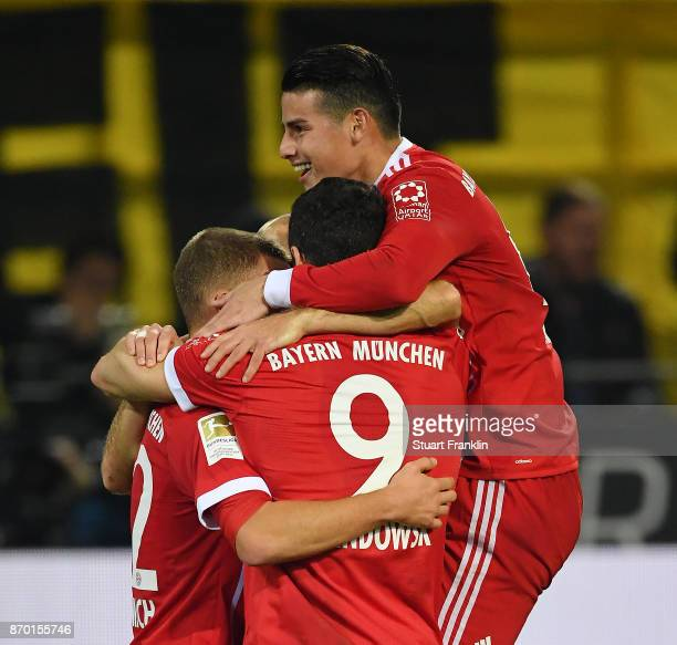 Robert Lewandowski of Bayern Muenchen celebrates with tea mates after he scored a goal to make it 02 during the Bundesliga match between Borussia...